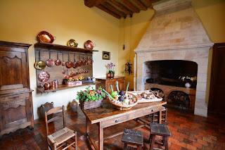 La cuisine est rustique, avec son sol en tomettes de terre cuite et l'imposante cheminée. Les ustensiles en cuivre rappellent la fonction première du lieu.