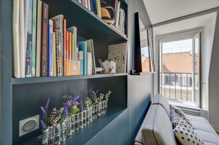 Salón con librería integrada en la pared en azul petróleo