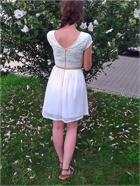 Biała sukienka, pasek z kokardką, sandały z ćwiekami, złoty medalik, asymetryczny warkocz