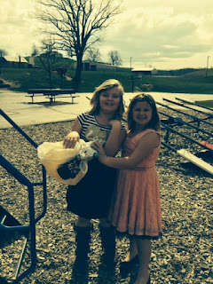Two young girls one holding a plastic bag with egg project