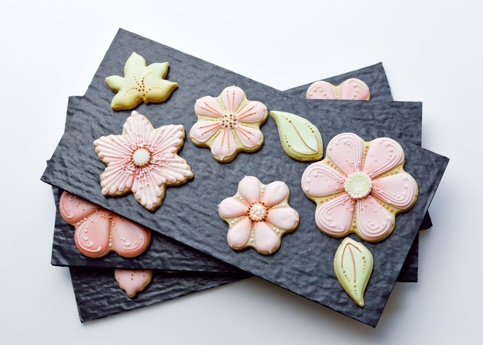 Layers of chocolate box cushion padding arranged with flower cookies, by Honeycat Cookies