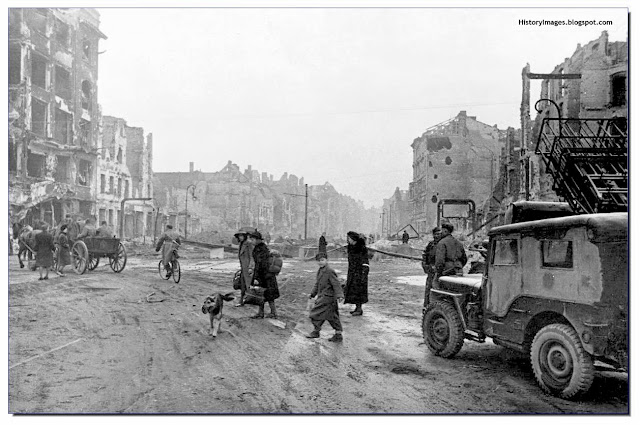 A destroyed Berlin in May 1945. German civilians walk dazed as the occupying Russian soldiers look on