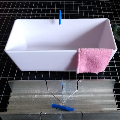One-twelfth scale modern miniature bath with pink towel over the side and blue tap over the back, sitting on a cutting mat with a miniature mitre box in front of it.