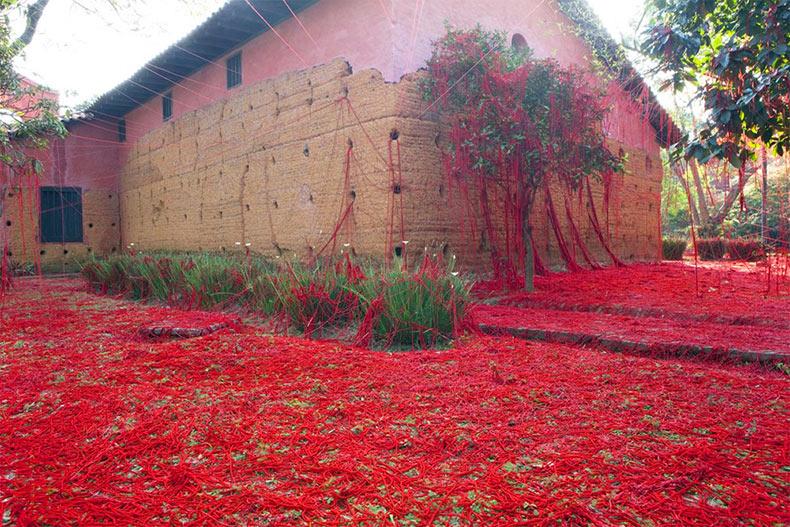 Una masa de enredados hilos rojo se deshacen de un telar para rebasar una capilla de Brasil