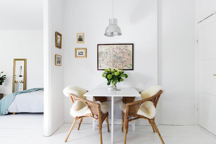 pequeño comedor con mesa plegable y sillas de mimbre