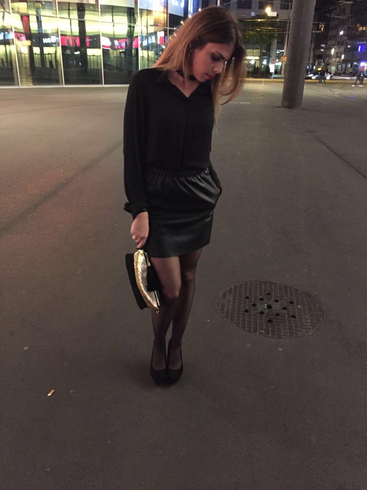 Lederjupe und schwarzes Top mit goldiger Clutch