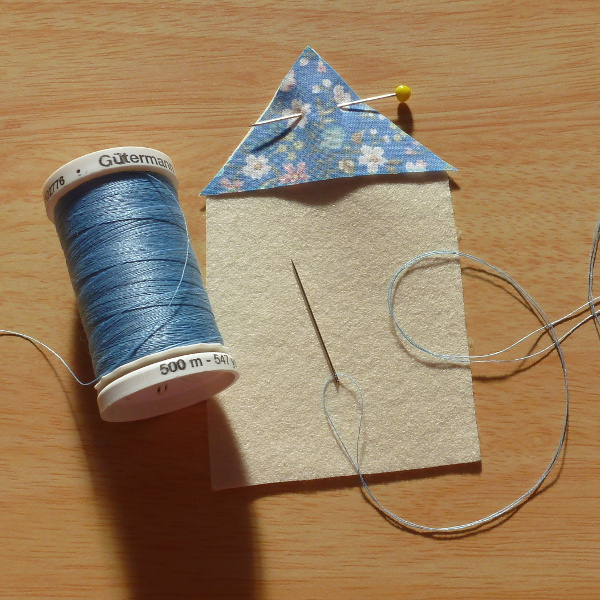 Pinned a blue patterned fabric triangle on to make a roof for a felt house blue sewing thread and needle