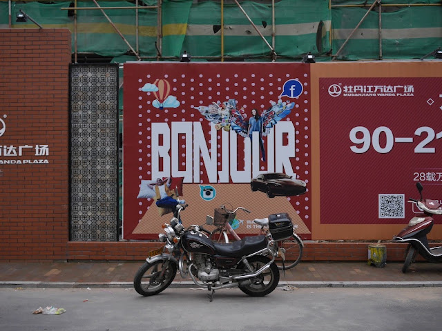 "Wanda Plaza ""Bonjour"" sign on a wall bordering a construction site in Mudanjiang, China"