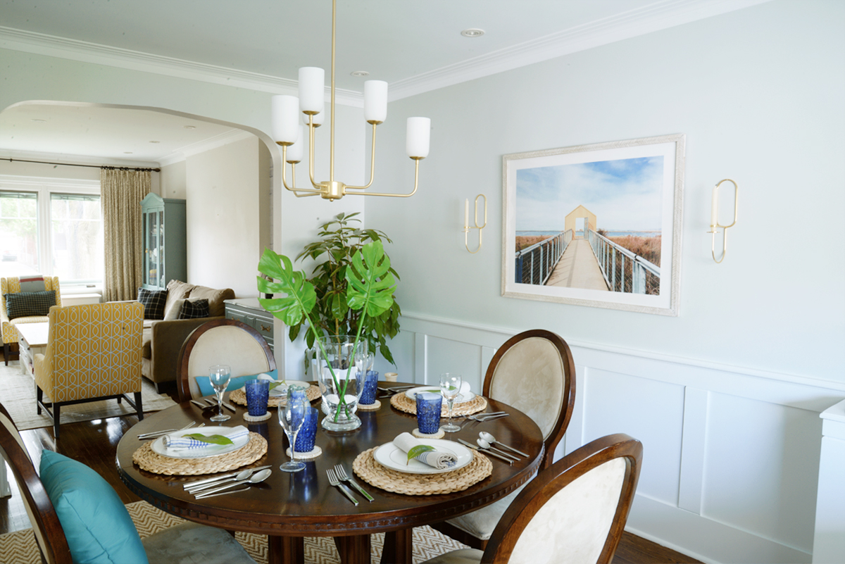 Rambling Renovators | tropical dining room, round dining table, Hinkley Harlow chandelier, blue and rattan