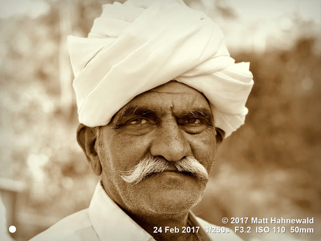 matt hahnewald photography; facing the world; character; face; eyes; eyebrows; deep-set eyes; facial expression; eye contact; moustache; turban; consent; rapport; respect; ethnic; traveling; rural; village; traditional; cultural; mela; pilgrim; shivratri mela; bhavnath; junagadh; gujarat; asian; indian; rabari; western india; one person; male; adult; elderly; man; picture; photo; face perception; physiognomy; nikon d3100; nikkor af-s 50mm f/1.8g; prime lens; 50mm lens; 4x3 aspect ratio; horizontal orientation; street; portrait; closeup; headshot; seven-eighths view; outdoors; sepia; vignette; posing; authentic; determined; manly; serious; photoshop; photoscape