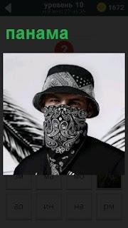 Мужчина одет в серую панаму и лицо спрятал в платок, остались только глаза и лоб