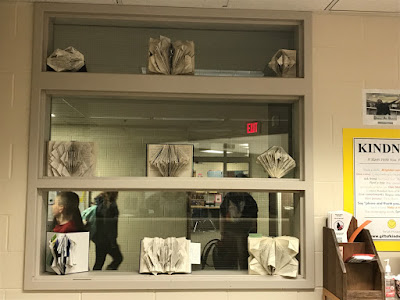 Display of weeded book art projects in window