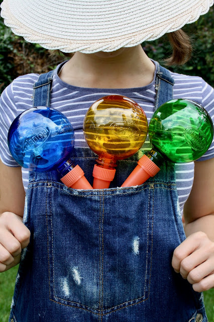 Abbey carries three Plantpal watering globes in the front pocket of her denim dungarees
