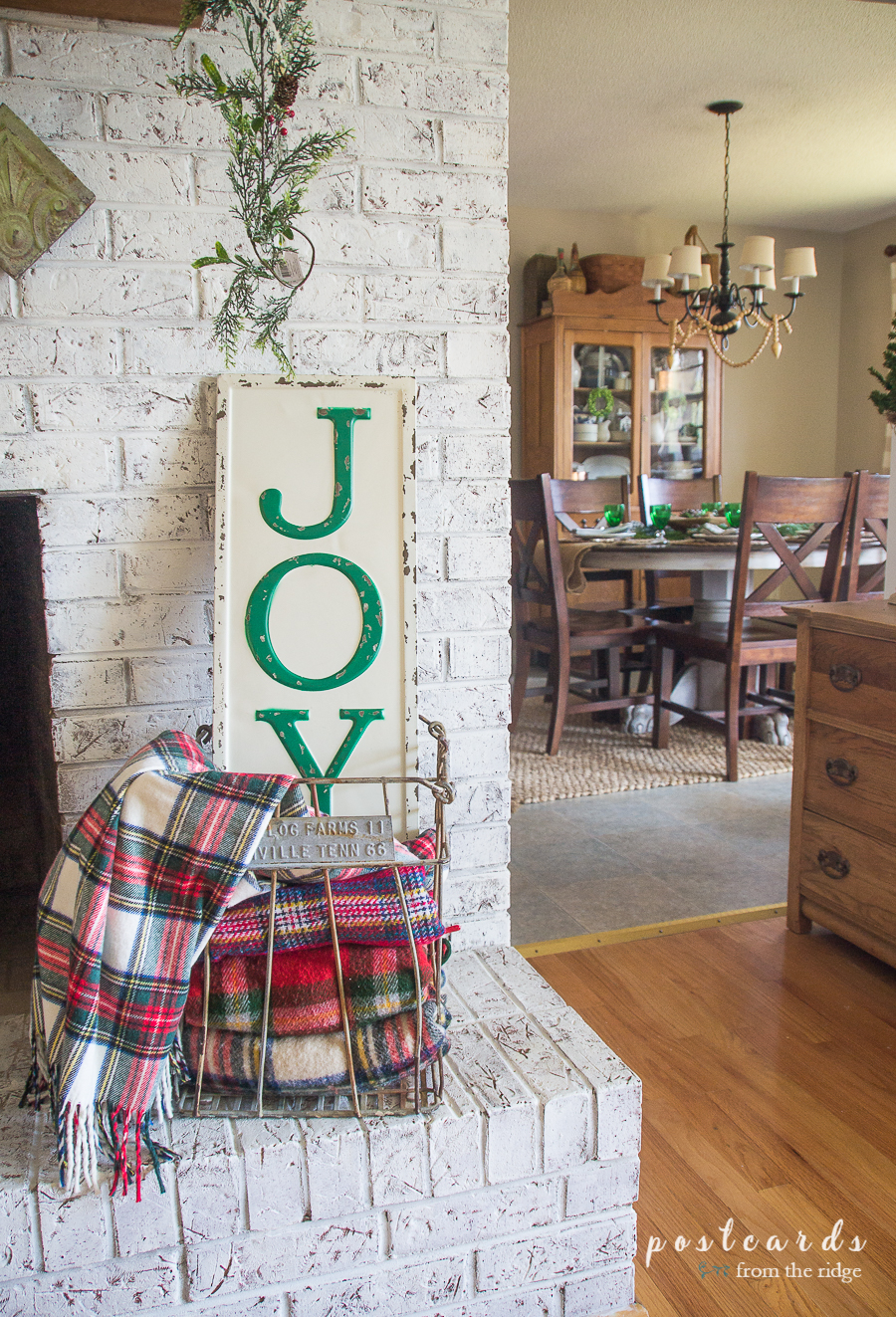 JOY metal sign on a farmhouse style painted brick fireplace
