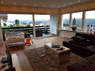 Blick in das renovierte Wohnzimmer mit Couch, TV- Bereich und Kinderecke