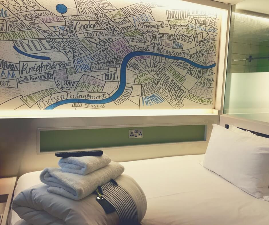 hotel room at Hub by Premier Inn, towels and sheets folded on the bed, an art installation of the Thames on the wall.