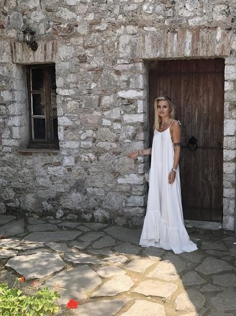 Biała sukienka maxi długa z odkrytymi plecami projektu Pola Rudnicki plecy odkryte projektantka suknia oversize wycieczka wakacje letni outfit ootd Albanii Albania Park Narodowy Butrint travel podróżowanie blogerka podróże moda zwiewna suknia Guess torebka klapki deichmann kapelusz zara