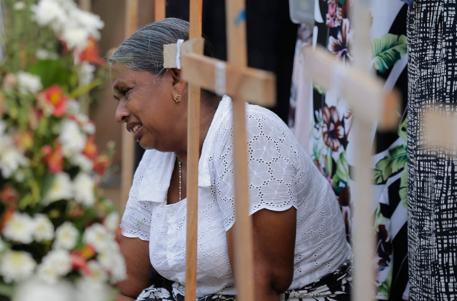 A Sri Lankan woman cries Wednesday as she sits next to the grave of a family member who died in an Easter Sunday bombing at a church in Negombo, Sri Lanka.
