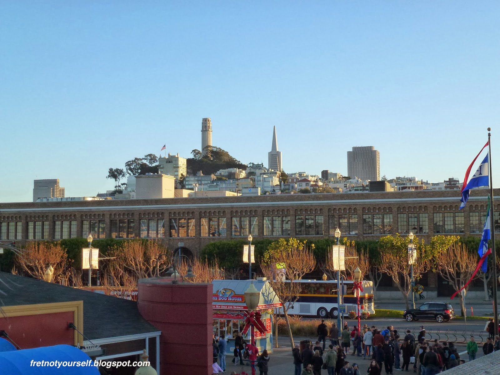 Coit Tower pierces the blue sky to the left of the Transamerica building. Buses, cars and many people are visible in the foreground.