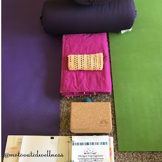 Two yoga mats are parallel to each other and between them are yoga bolsters, a blanket, eye bag, and yoga block. Yoga teacher training manual in a binder sits open next to the mats and yoga props.