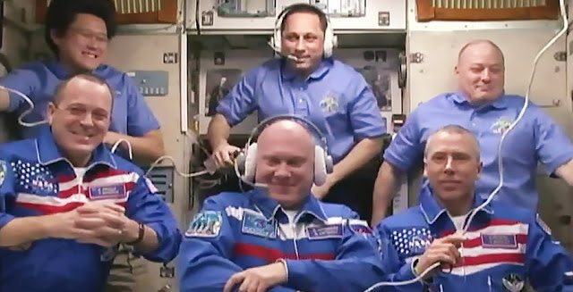 The newest Expedition 55 crew members (front row from left) Drew Feustel, Oleg Artemyev and Ricky Arnold gather in the Zvezda service module and speak to family and colleagues back on Earth. Behind them are (from left) Norishige Kanai, Commander Anton Shkaplerov and Scott Tingle. Credit: NASA TV