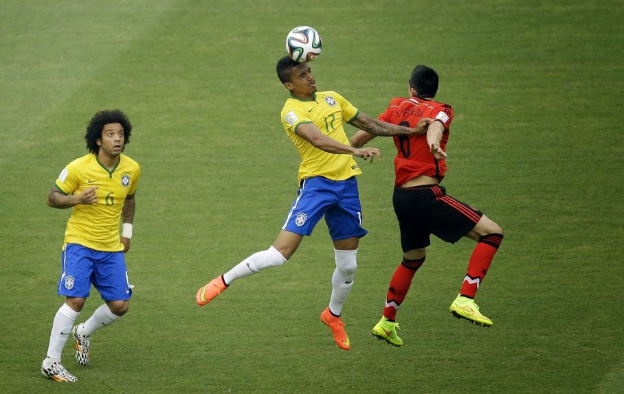 Brazil's Marcelo, left, looks on a Brazil's Luiz Gustavo and Mexico's Hector Herrera, right, go for a header during the group A World Cup soccer match between Brazil and Mexico at the Arena Castelao in Fortaleza, Brazil, Tuesday, June 17, 2014.