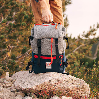 a man on a hike carrying a topo designs wool backpack