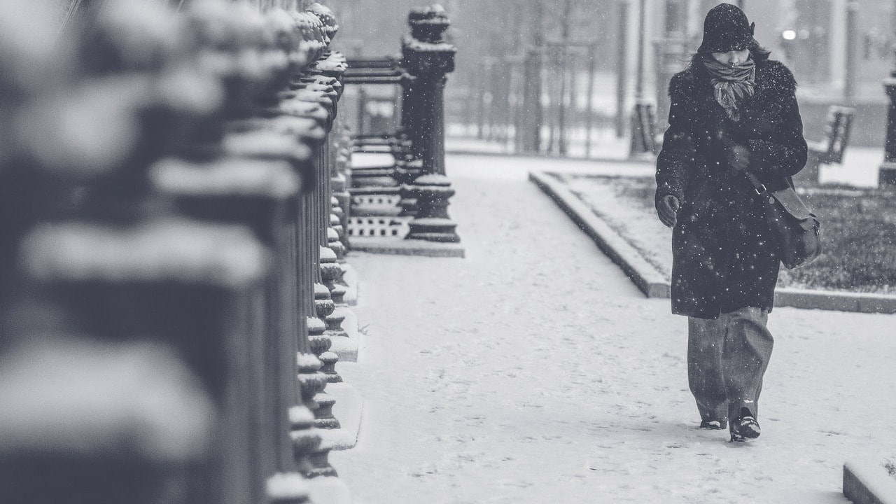 Calle nevada con mujer de principos de siglo XX