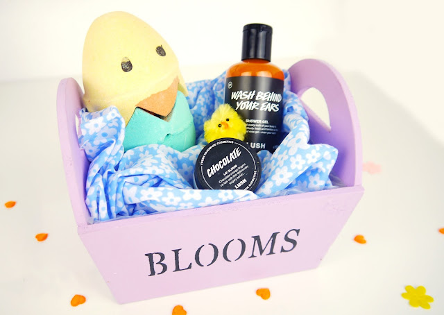 chick shaped bath bomb, orange shower gel, and jar of lip balm sat in a lilac basket