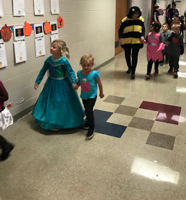 Young girl in a long blue princess dress walking and holding a young girls hand