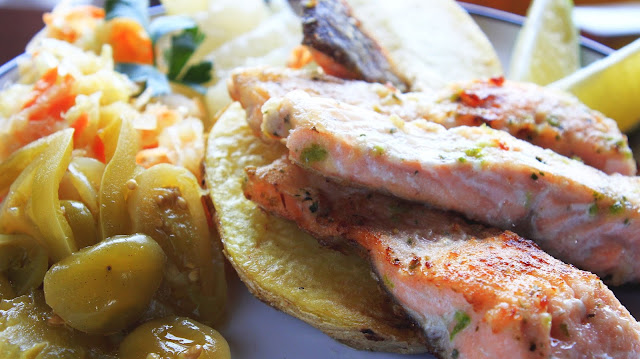 Pstrąg łososiowy na talerzu w towarzystwie ziemniaków,surówki z kiszonej kapusty, pikli i zielonych pomidorów.