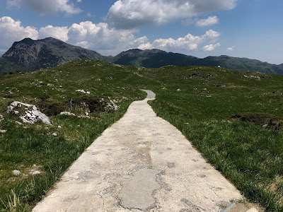 Road leading to and from Rifugio Gherardi with Monte Cancervo in the distance, left.