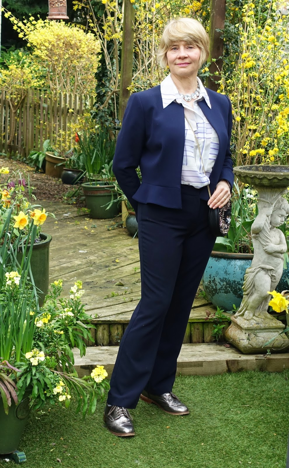 A look suitable for the office with the blouse paired with navy trousers, a navy peplum jacket and metallic brogues.