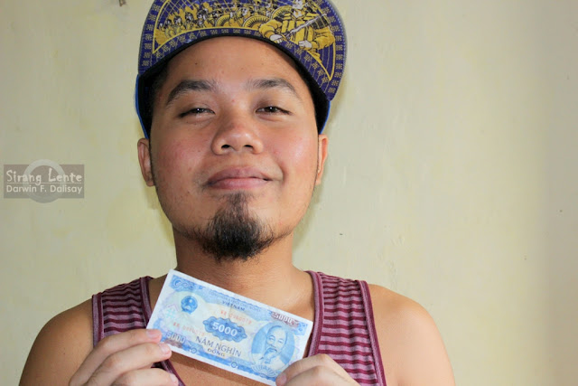 Darwin Dalisay holds a Dong, a Vietnam Currency