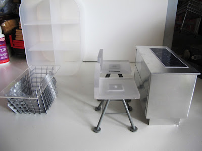 Modern dolls' house miniature set up with a metal kitchen unit with stove, white and grey bar stools, grey and perspex coffee table and a white perspex shelving unit.