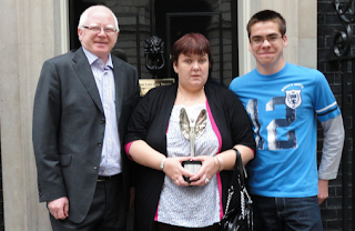 Image: Julie Coghill outside 10 Downing Street with her husband Philip and son Conor with her Pride of Britain Award. ©: courtesy of Philip Coghill