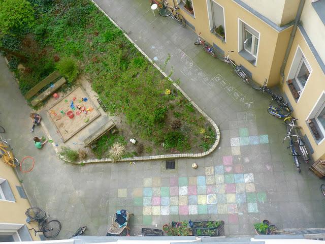 Luftbild: Hinterhof mit Sandkasten, Bäumen, Büschen, blühenden Blumen, Fahrrädern und bunter Pflastermalerei