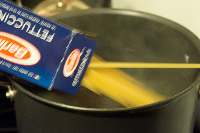 Pasta being added to a pot of boiling water.