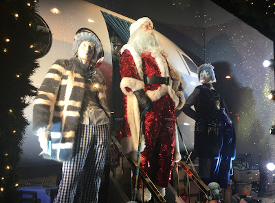 Pic of sequinned Santa coming down steps of jet plane with adult companions