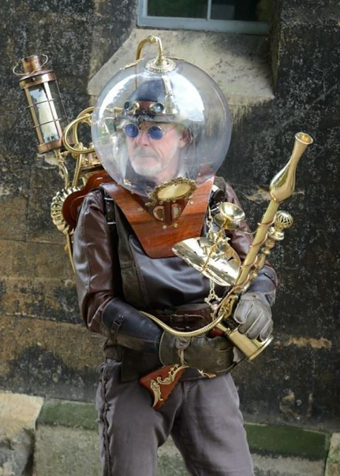 Man dressed as a steampunk space explorer or astronaut with big glass helmet dome, brass gun, backpack and more. men's steampunk clothing and costumes