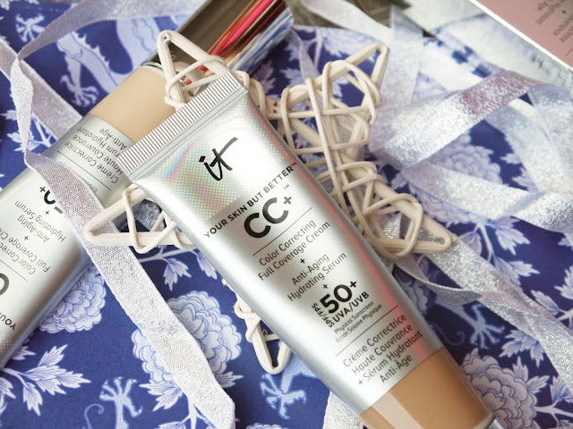 Silver tubes of IT Cosmetics CC cream on a blue floral background