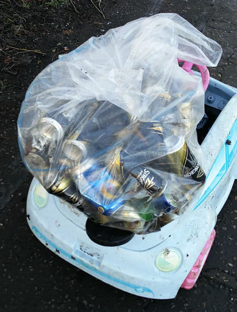 A sack of beer cans and a child's toy car