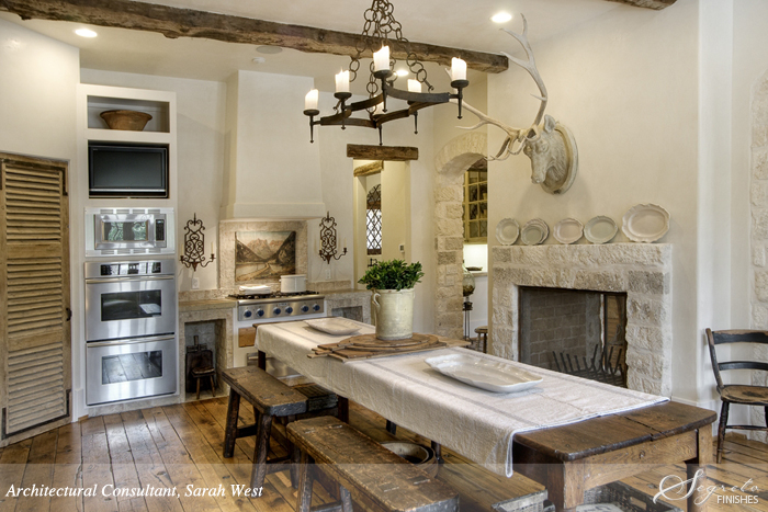 Antique French farmhouse table and benches in a European country rustic kitchen with Segreto Finishes.