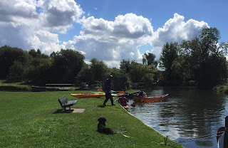 Photo of me lying on grass just to the front of our floatyboaty home watching a group of humans with canoes and kayaks.