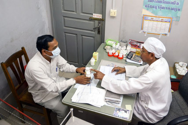 A Cambodian doctor (right) offers antiretroviral drugs to a man who is living with HIV at Phnom Penh's Khmer-Soviet Friendship hospital in 2012. Tang Chhin Sothy/AFP