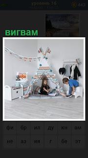 дети сделали вигвам в комнате, играют между собой