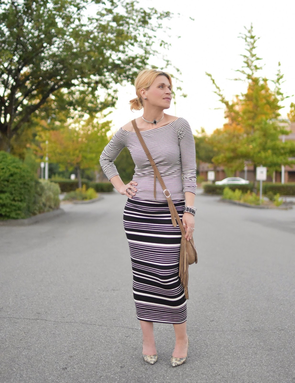 Monika Faulkner styles a striped midi pencil skirt with a striped off-the-shoulder top, reptile pumps, and fringy cross-body bag