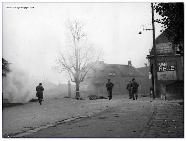 German soldiers walk the streets of the Dutch village of Wagenborgen as dead Dutch soldiers lie. May 1940