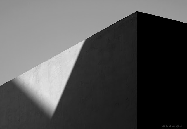 A Black and White Minimal Art Picture of an Inverted Light Triangle formed by Light on the walls of Jantar Mantar, Jaipur, India.