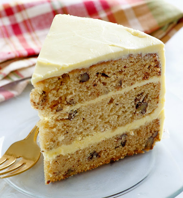 slice of triple layer cake studded with nuts and smooth frosting